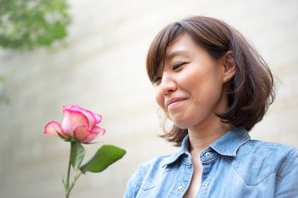 一輪のバラを持つ女性