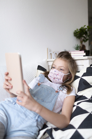 young girl with pink protective mask at home in her room in quarantine with a tablet during corona covid 19 crisis