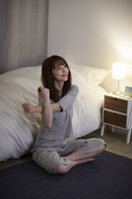寝室でストレッチをする日本人女性