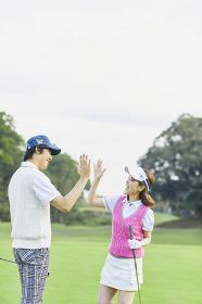 ゴルフ ハイタッチをする日本人カップル