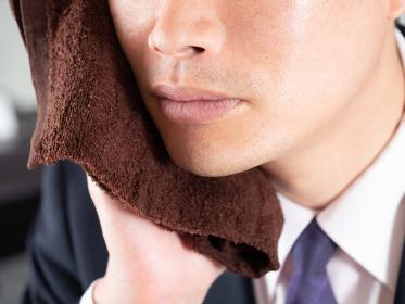 ヒゲ脱毛の後に毛穴を冷やす男性ビジネスマン