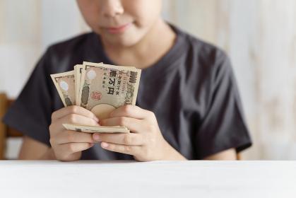1万円札を数える小学生の男の子