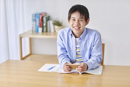 スマートフォンを見て勉強する男子中学生
