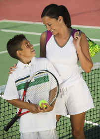 Mother and son by net on tennis court high angle view