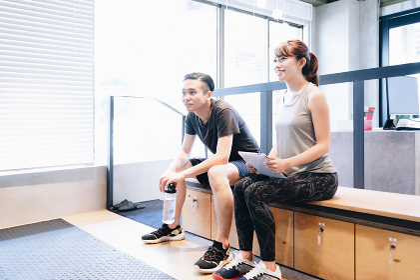 スポーツジムで座って休憩をする若いカップル