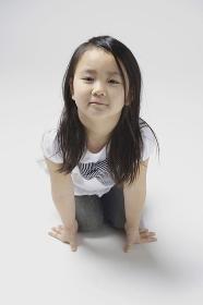 床に座り手をつき微笑む6歳の女の子