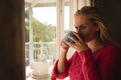 Thoughtful caucasian woman standing by sunny balcony window drinking coffee. spending free time at home.