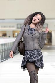 商業施設でグレーのライダースジャケットとはおりチェック柄のワンピースを着て編み上げのブーツを履いたワッフルヘアの笑顔の女性が少し首を傾けながら楽しそうにこちらに歩いてくるシーン
