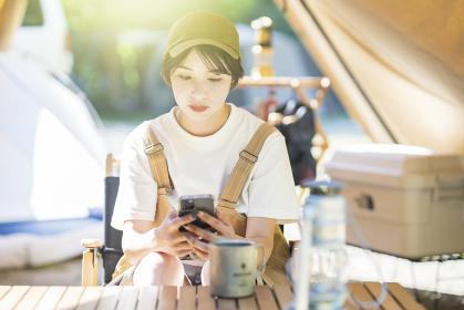 キャンプをして、テントの中でスマートフォンを操作する若い女性