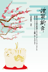 トラの置物と梅の花と雲が背景にある年賀状イラスト