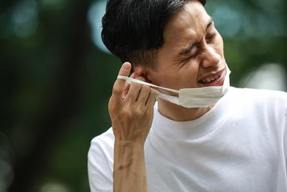 マスクを着け耳が痛む男性