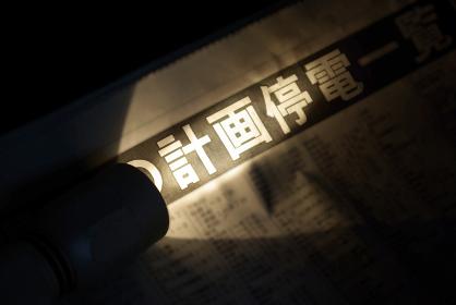 懐中電灯で照らされた「計画停電」の新聞見出し