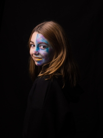 Young girl (10-12 years) with half face make up on black background.