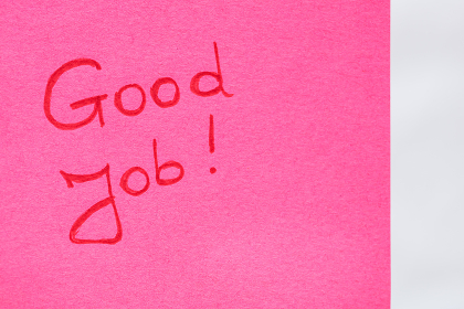 Good job handwriting text close up isolated on pink paper with copy space. Writing text on memo post reminder