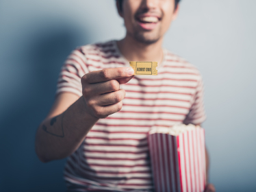 A happy young man with a box of popcorn is holding a cinema ticket