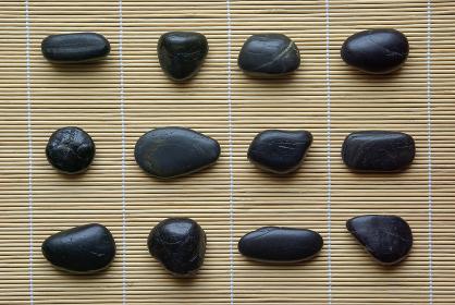 巻き簾の上に並べた12個の黒い石