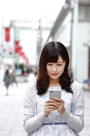 歩きスマホをする若い日本人女性