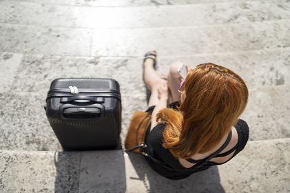 top view of red hair girl sitting on stairs next to luggage under sun