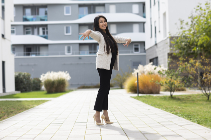 Woman with high heels  dancing outside in front of new buildings