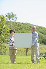 メッセージボードを持つシニア夫婦