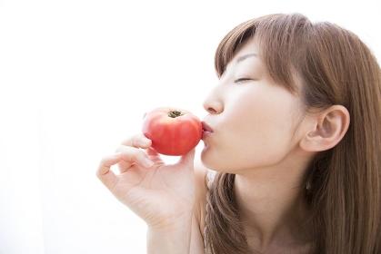 トマトにキスをする女性