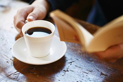 本を読む男性とコーヒー