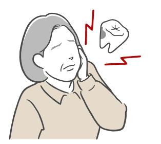 虫歯が痛くてほっぺたを押さえる中年女性