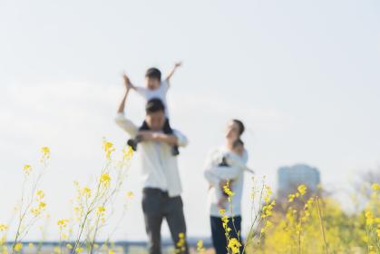 笑顔で野原を散歩する親子をアウトフォーカスで撮影