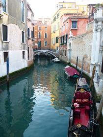 イタリア・ヴェネツィアにて細い水路と2人乗り用の黒い無人ゴンドラ