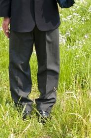 草むらを歩く男子高校生の足元