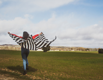 young woman in the field with striped blanket moving in the wind