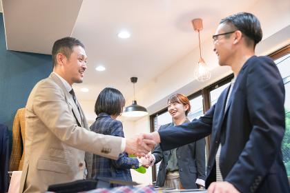笑顔で握手をする4人の人物
