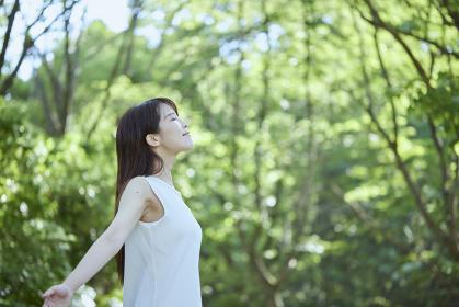 森の中でリラックスする若い日本人女性