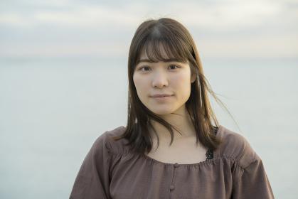 夕方、海をバックに撮影された若い女性のポートレート