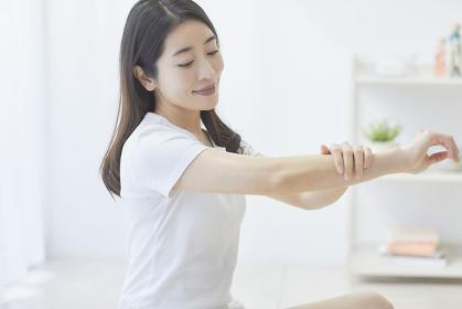 腕をマッサージする日本人女性