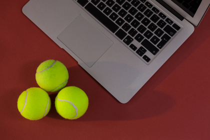 High angle view of tennis balls by laptop