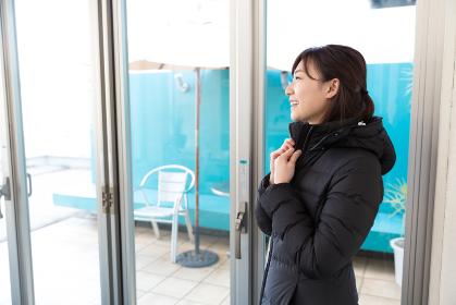 部屋でコートを着た女性