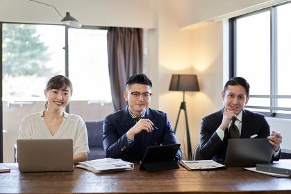 カメラ目線で笑顔のアジア人とラテン人のビジネスパーソン