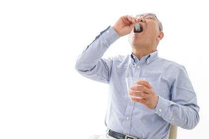 薬を飲む高齢男性