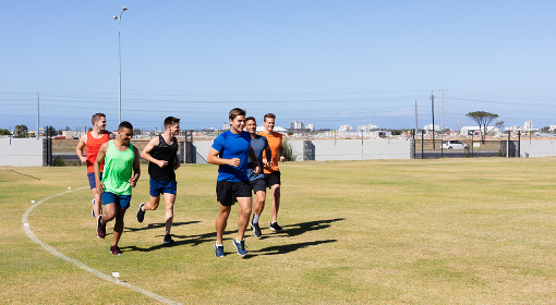 Front view of a multi-ethnic group of male runners training at a sports field, running together on a grass track