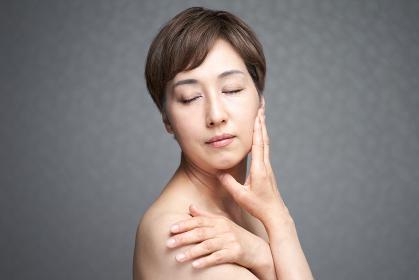 頬と肩を押さえる中年の日本人女性