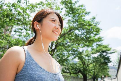 音楽を聴きながらランニングする若い女性