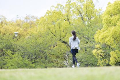 自然豊かな公園をランニングする若い女性
