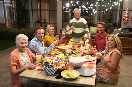 Multi-generation Caucasian family enjoying their time at home together, sitting by a table, talking, looking at the camera and smiling, making a toast