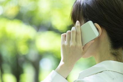 新緑の中でスマートフォンを使う若い女性の手元