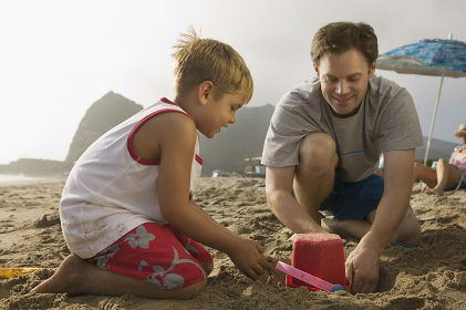 Boy And Father Building Sand Castle At Beach