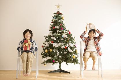 椅子に座りプレゼントを持つ子供達とクリスマスツリー