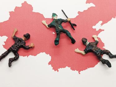 赤い中国の地図の上で倒れている兵士たち