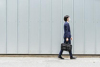 マスクをして歩く若いビジネスマン(通勤・外回り)・コピースペースのある画像