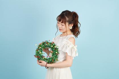 クリスマスリースを手に持つ女性